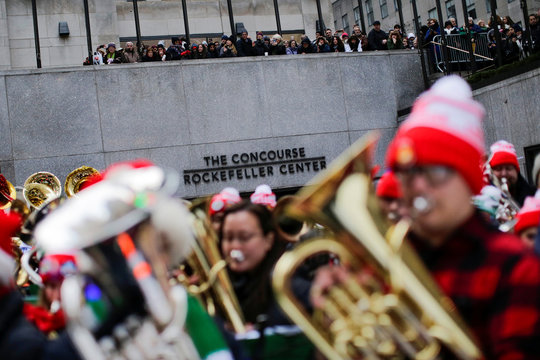 People watch hundreds of tuba players perform Christmas carols at 44th Annual Merry Tuba Christmas at Rockefeller Center in the Manhattan borough of New York