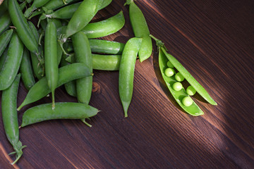 green pea pod on a wooden background