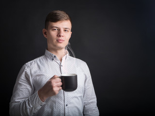 Stylish man in white shirt holds cup in his hand. Handsome man in business clothing, holds cup with hot coffee or tea. Advertising for cafe or bistro. Copy space. Young man holding a mug of hot drink.