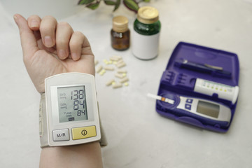 On the arm is a medical device that measures blood pressure. On the table is a glucometer and tablets.