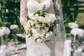 Bride holding beautiful white and green bouquet on the wedding.