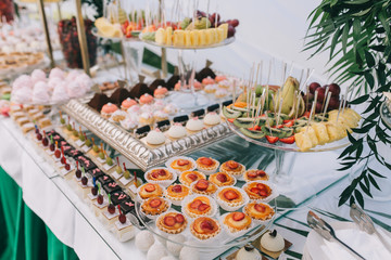 Beautiful wedding sweet buffet with decor and green.