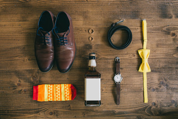 Wedding groom accessories in yellow. Shoes, whiskey, rings, bouquet, watches, straps and socks in a top view.