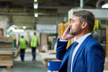 Side view portrait of handsome mature businessman speaking by phone in factory workshop with two workers in background, copy space