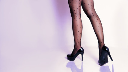 Attractive female legs in fashionable dotted pantyhose