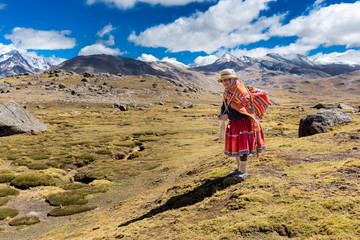 Peruvian indigenous old woman standing weaving traditional cloths, Peru.