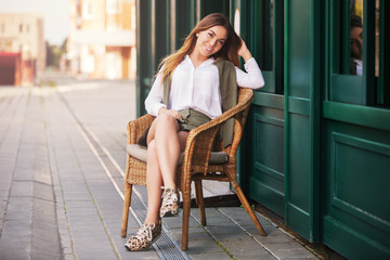 Young fashion woman in white blouse sitting on wicker chair against a sidewalk cafe