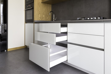 Opened kitchen drawer, kitchen in a modern loft style with wooden elements, grey ceramic countertop and backsplash.