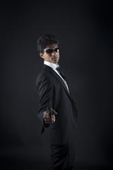 Secret agent pose for an asian man wearing a smoking