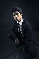 Secret agent man posing on black background