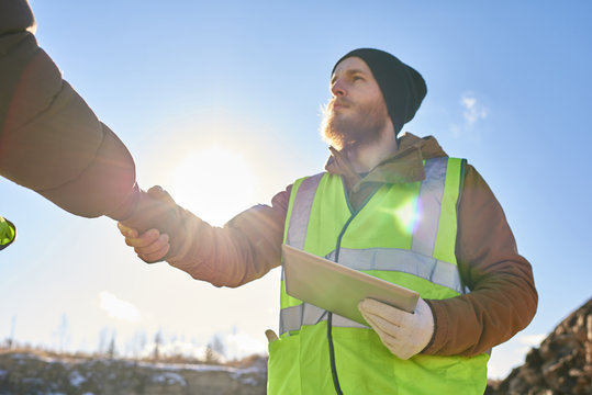 Low angle portrait of bearded industrial worker wearing reflective jacket shaking with partner hands outdoors against cold blue sky