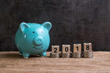 Year 2018 financial goal with piggy bank and stack of coins and on top by wooden cube block with number 2018 on table and dark black background with copy space