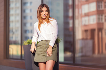 Young fashion woman in white blouse and short skirt in a city street