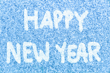 HAPPY NEW YEAR text message hand written on blue ice frosted window background in white snow. Photo of real snowflakes texture frozen outside with handwriting happy new year painted on top. 2018.