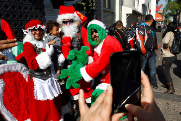 Motorbikers dress up as Santa, pose for a photograph with a child during annual motorcycle club rides delivering presents to poor children through the streets in Tijuana