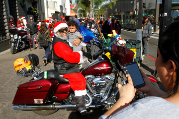 Motorbiker dress up as Santa, poses for a photograph with a child during annual motorcycle club rides delivering presents to poor children through the streets in Tijuana