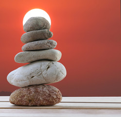 Balance Stones stacked to pyramid in the sunset background and have copy space.