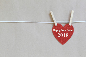 Red heart hanging on a rope and have happy new year 2018 text.