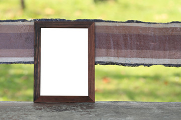 Wooden empty of picture frame placed on the bench in the park.
