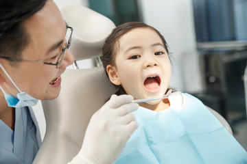 The dentist is examining the tooth for the little girl