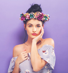 Beautiful young woman with a garland on a solid background
