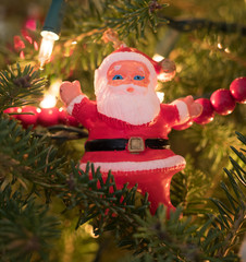 Vintage Plastic Santa Ornament in a red suit with red bead garland, lights and a Christmas tree in the background.