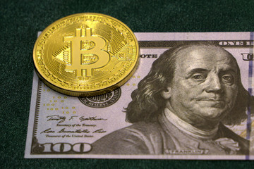 A symbolic coins of bitcoin on banknotes of one hundred dollars. Exchange bitcoin cash for a dollar.