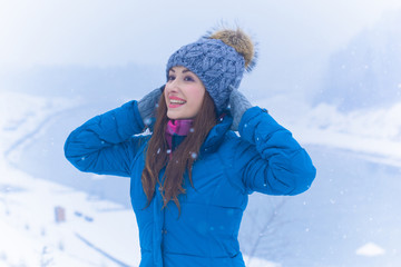 Young cute woman rests on a winter vacation in the mountains, a fun and beautiful winter time. A girl in a snow-covered forest and mountains. Active and joyful outdoor recreation