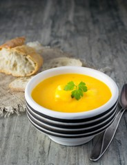 A bowl of pumpkin potato vegetable soup with bread and garnish on a rustic wooden background