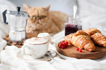 Breakfast in bed with croissants, coffee and jam.