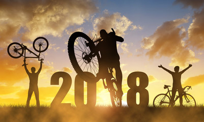Cyclist with bicycle at sunset.Forward to the New Year 2018.