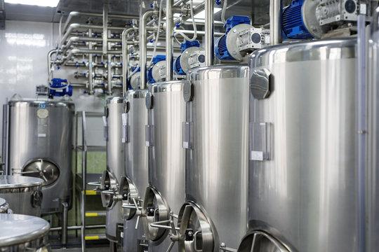 A series of gray metal tanks for mixing liquids.