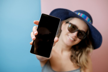Young woman in hat and sunglasses with phone