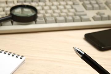 ビジネスイメージ ペンとスマートフォンとパソコンと虫眼鏡
