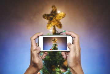 Hands holding mobile smart phone, taking photo of Christmas star on Christmas tree with colorful lights