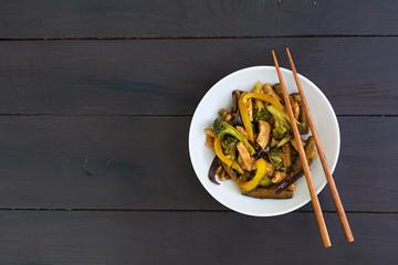 Stir fry chicken, broccoli and pepper on dark background