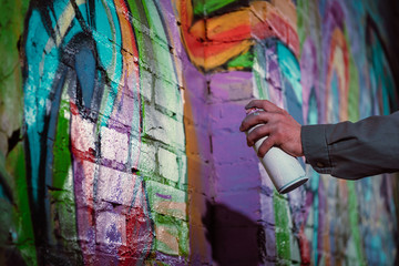 cropped view of street artist painting graffiti with aerosol paint on wall at night