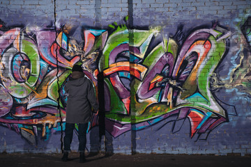 Foto op Canvas Graffiti back view of street artist painting colorful graffiti on wall at night