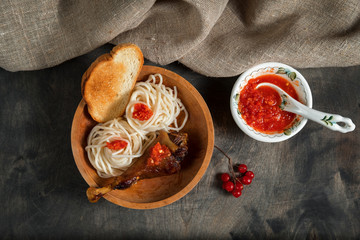 dish is grilled chicken with spaghetti and spicy tomato sauce in a wooden bowl on a dark wooden table and the background linen burlap