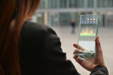 A business woman in the city, use the transparent phone with the latest technology with holography and watch the weather and the messages. Concept: technology, future and futuristic technology.