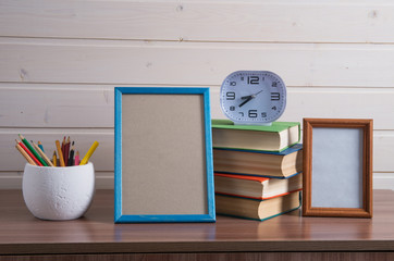 frame and pile of old books on wooden table