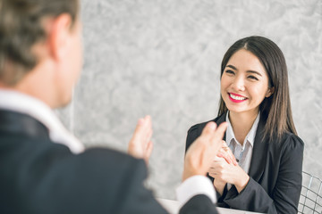 Boss/Business man employer admires young Asian business woman/staff/employee by thumb up and clap with smiling face for her success and good/best in work and recognition/appreciate. Wall mural