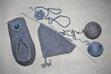 gray-blue knitted woolen slippers with flower and ties, knitting process of two tangles, female model
