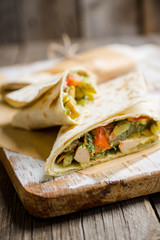 Shawarma with sauce on the rustic wooden background. Selective focus. Shallow depth of field.