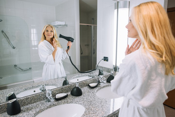 attractive mature woman in bathrobe drying hair with hair dryer in bathroom at hotel