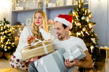 Photo of happy couple in Santa cap with gift in box