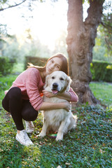 Photo of girl hugging dog on lawn