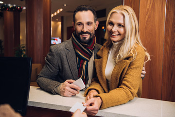 smiling mature couple holding smartphone and card at reception in hotel
