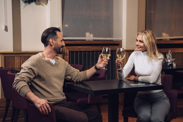 beautiful happy middle aged couple drinking wine and smiling each other in hotel restaurant