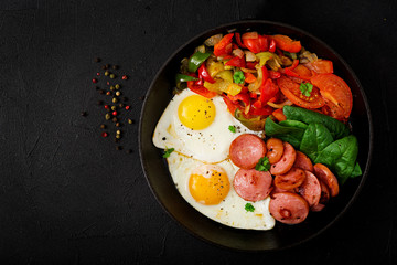 Breakfast. Fried eggs with sausage and vegetables in a frying pan on a black background in rustic style. Top view
